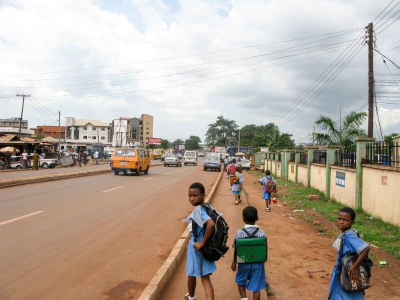 Rua nigeriana com crianças e carros da escola foto de stock royalty free
