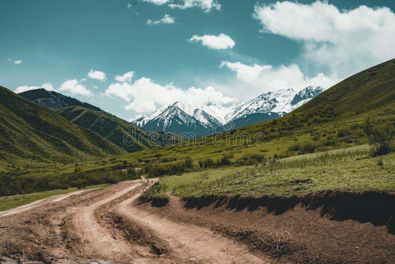 Rua no estepe com as montanhas de Tian Shan no fundo, central Ásia de Cazaquistão imagens de stock royalty free
