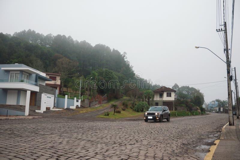 Rua pedra com casas e carros em um dia nevado imagem de stock royalty free