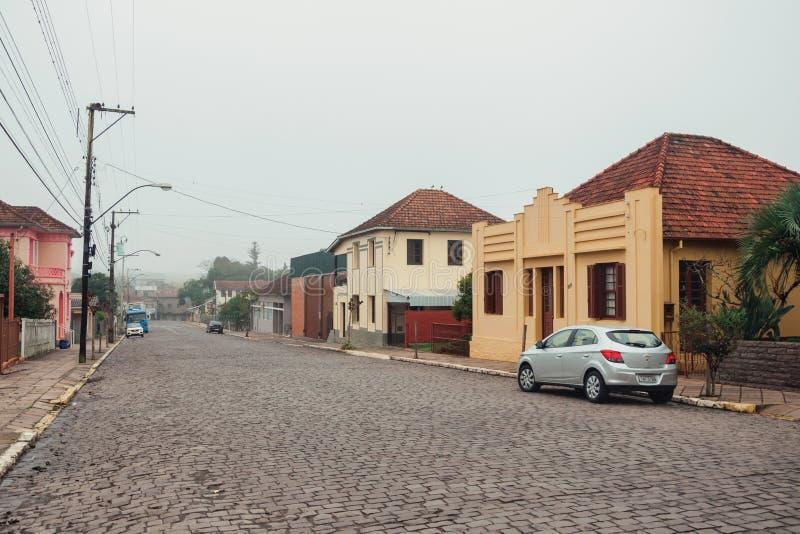 Rua pedra com casas e carros em um dia nevado foto de stock royalty free