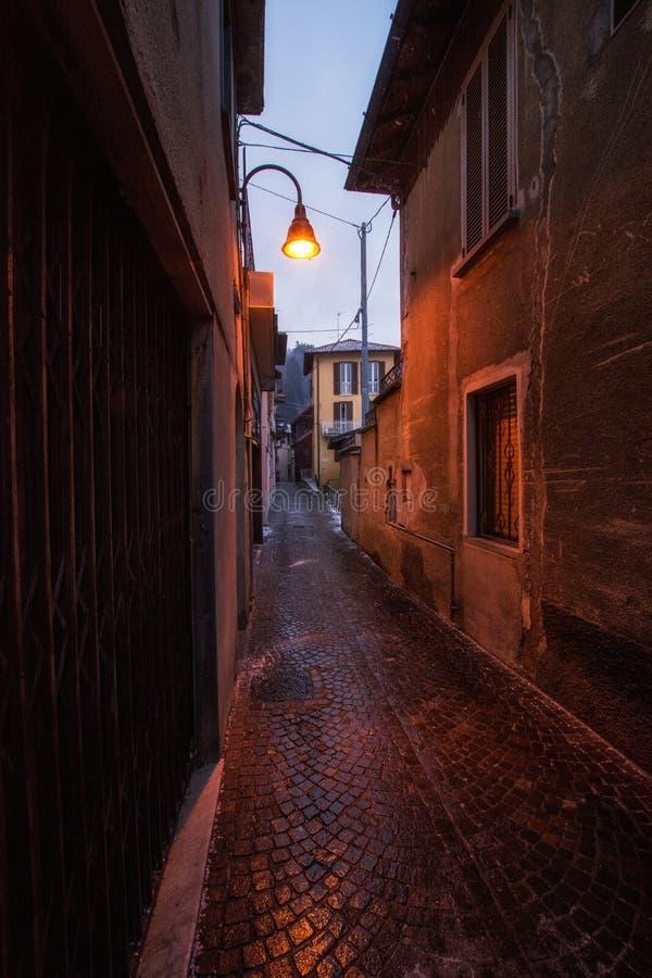 Rua pequena de Tipycal da cidade de Brunate, iluminada por uma lâmpada de rua, Como, Itália Rua escura foto de stock