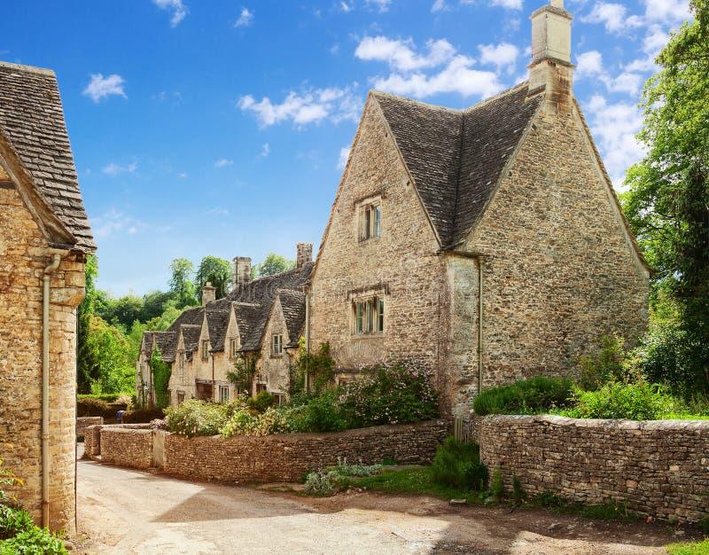 Rua velha com as casas de campo tradicionais de Cotswold em uma manhã ensolarada da mola, Bibury, Gloucestershire, Inglaterra, Re foto de stock