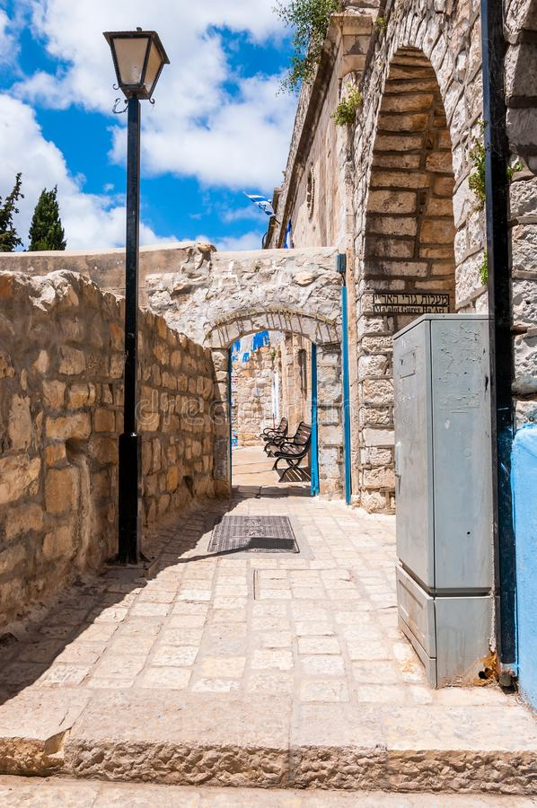 Rua velha da cidade de Safed, bystreet, aleia, backstreet com lanterna, bancos, paredes de pedra antigas, arcos e decorações bran imagens de stock royalty free