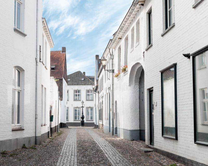 Rua velha vazia da cidade com construções pintadas brancas imagens de stock