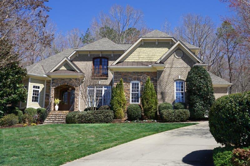 Rua-vista de uma casa suburbana com exterior de pedra em uma vizinhan?a afluente foto de stock