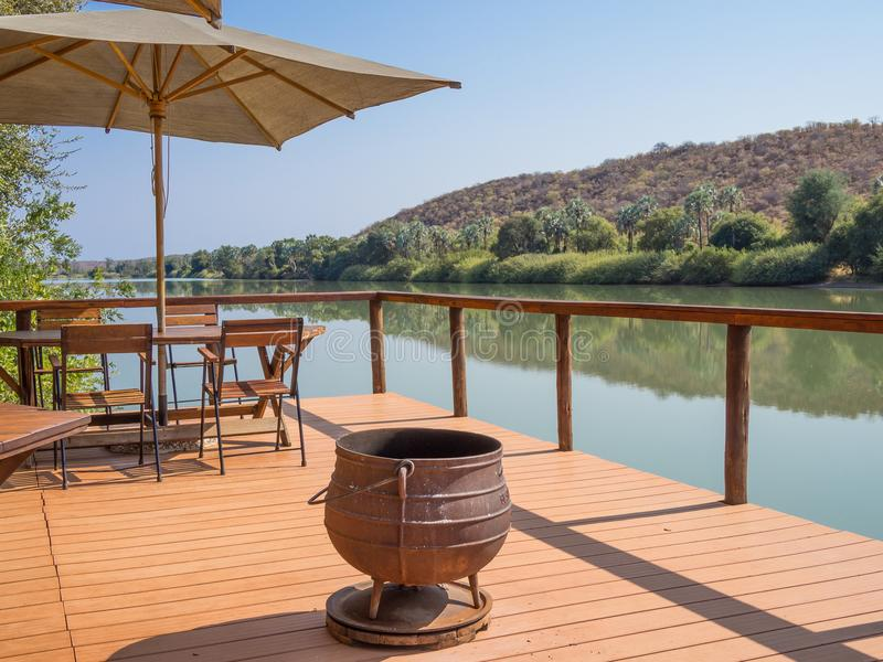 Ruacana, Namibia - July 22, 2015: Wooden terrasse with chairs, umbrealla, table and cast iron pot at Kunene River. Ruacana, Namibia - July 22, 2015: Wooden royalty free stock photos