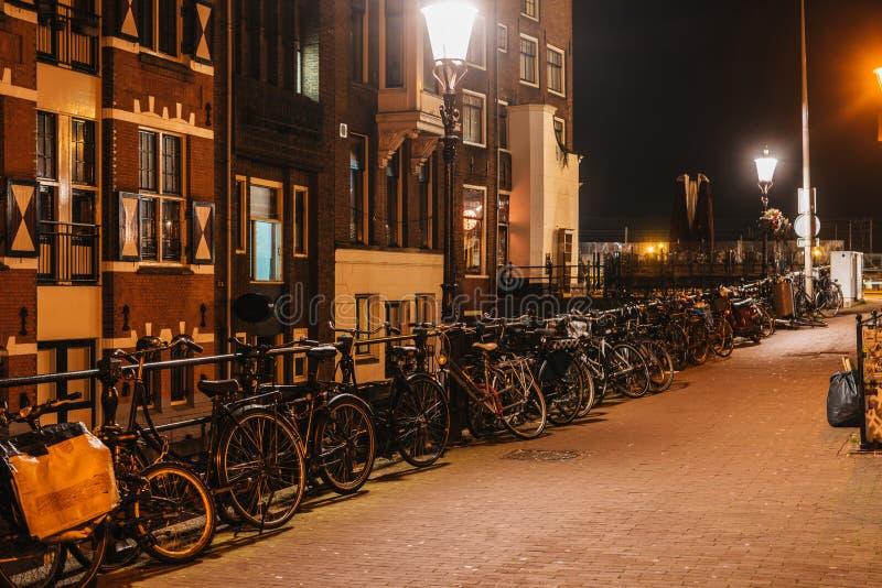Ruas acolhedores de Amsterdão da noite com estacionamento da bicicleta fotografia de stock royalty free