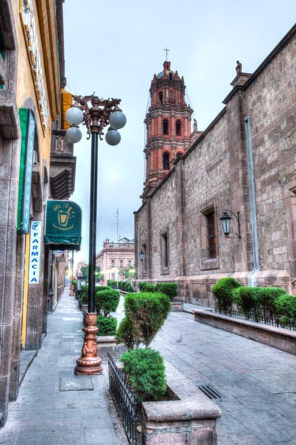 Ruas do centro de San Luis Potosi no nascer do sol com postes de luz imagens de stock