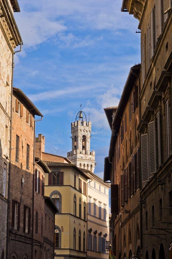 Ruas estreitas e construções velhas em Siena, torre de pulso de disparo no fundo imagens de stock royalty free