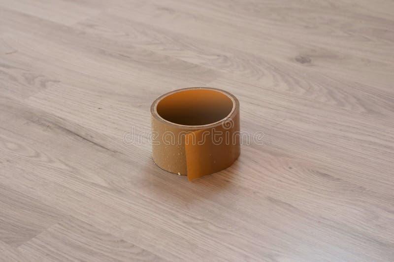 Ruban adhésif de Brown sur le fond en stratifié en bois image libre de droits