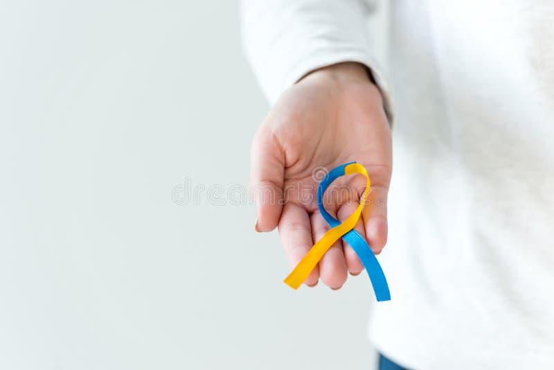 Ruban bleu et jaune de main de maintien de syndrome de symbole femelle de jour images libres de droits