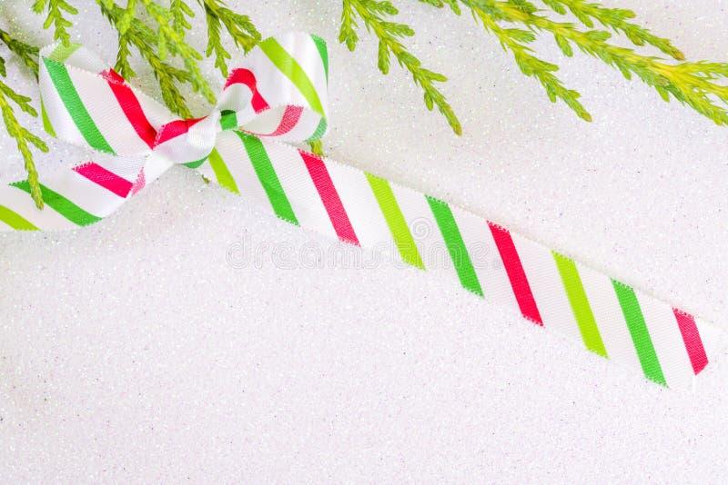 Ruban en soie rayé blanc, rouge et vert attaché dans un arc sur un petit morceau photo stock