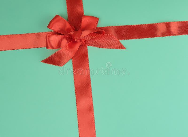 ruban en soie rouge étiré et arc attaché, fond vert image stock