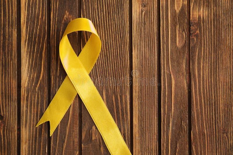 Ruban jaune sur le fond en bois Concept de conscience de Cancer photographie stock libre de droits