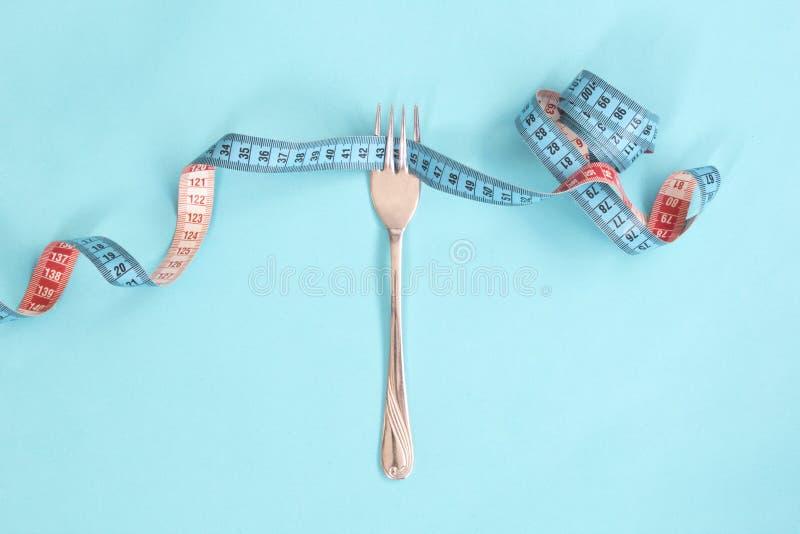 Ruban métrique autour d'une fourchette comme concept pour le régime La fourchette sont enveloppées dans la bande de mesure bleue  photo stock