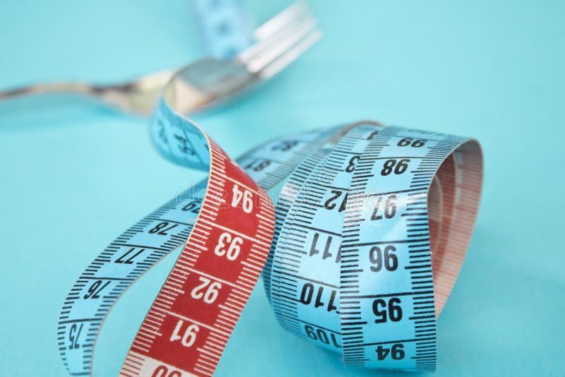 Ruban métrique autour d'une fourchette comme concept pour le régime La fourchette sont enveloppées dans la bande de mesure bleue  photographie stock