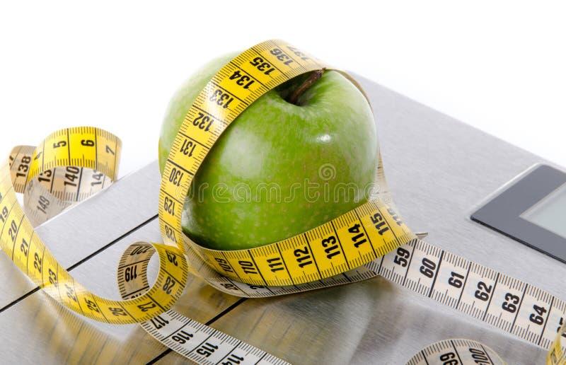 Ruban métrique autour d'une pomme verte sur des échelles de salle de bains image libre de droits
