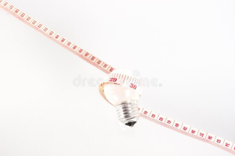 Ruban métrique autour de la lampe photographie stock