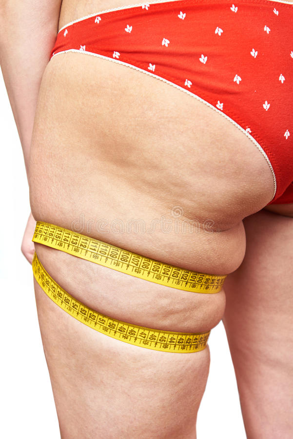 Ruban métrique de mesure de jambe de cuisse de grosse femme image stock
