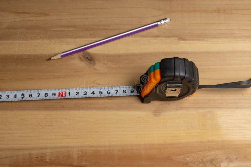 Ruban métrique et crayon sur le fond d'un morceau de bois photographie stock libre de droits