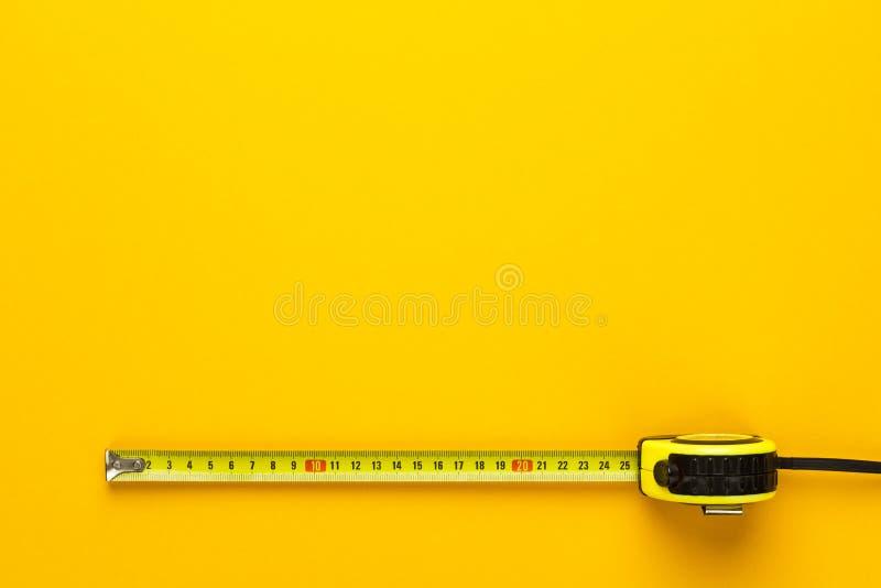 Ruban métrique sur le fond jaune photographie stock libre de droits