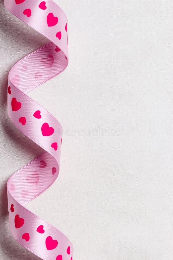 Ruban rose de coeur sur le fond de tissu photographie stock