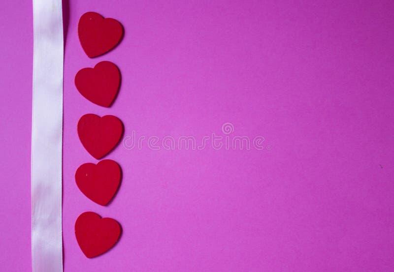 Ruban rose et coeurs rouges sur le fond rose Fond de jour de valentines photo libre de droits