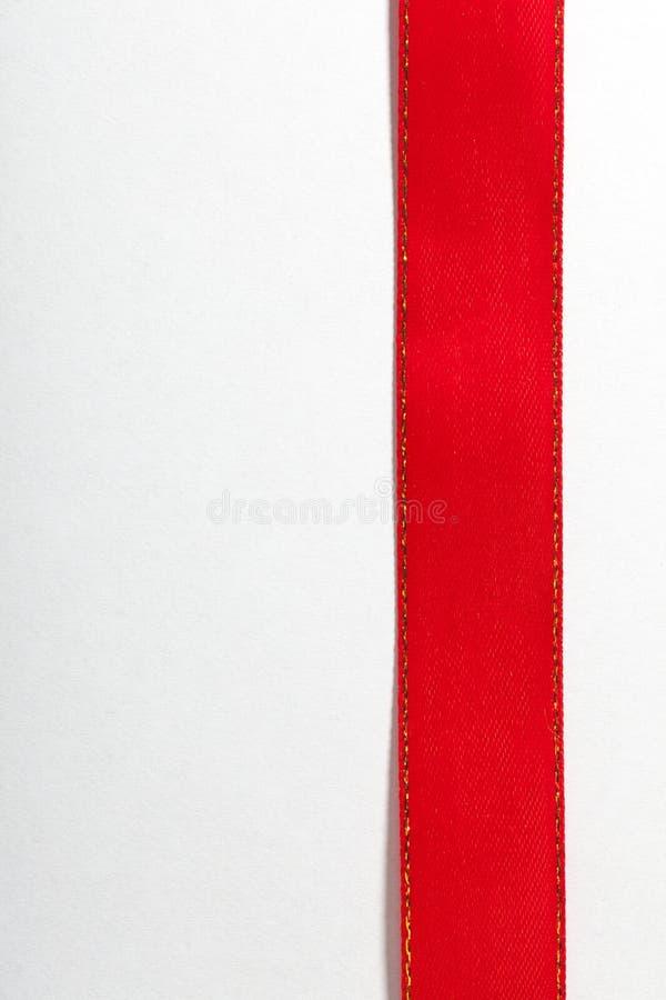 Ruban rouge brillant sur le fond blanc avec l'espace de copie. photo stock