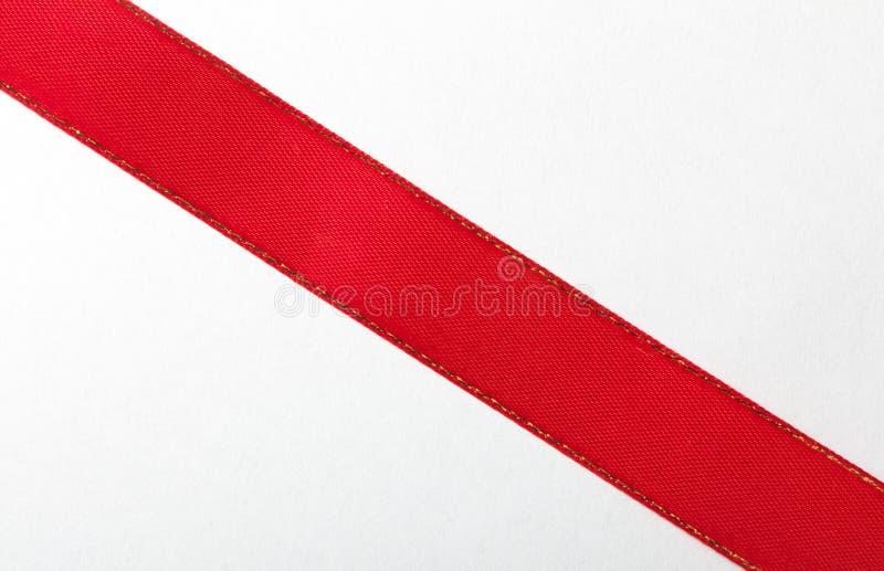 Ruban rouge brillant sur le fond blanc avec l'espace de copie images libres de droits