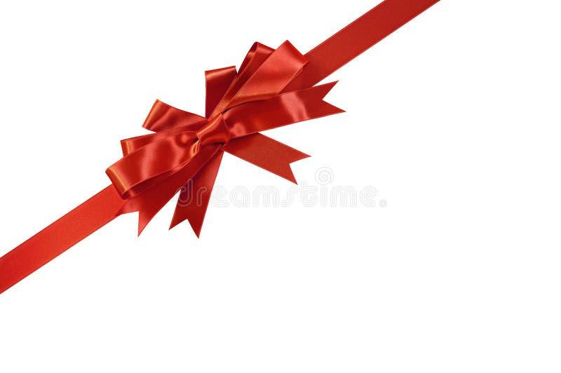 Ruban rouge diagonal faisant le coin de cadeau d'arc d'isolement sur le blanc images stock