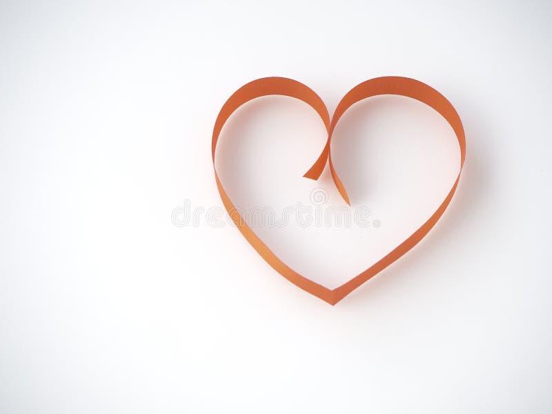 Ruban rouge en forme de coeur sur un fond blanc photo stock