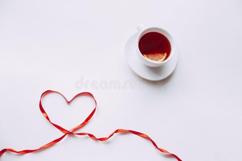 Ruban rouge sous forme de coeur avec la tasse de thé photos stock