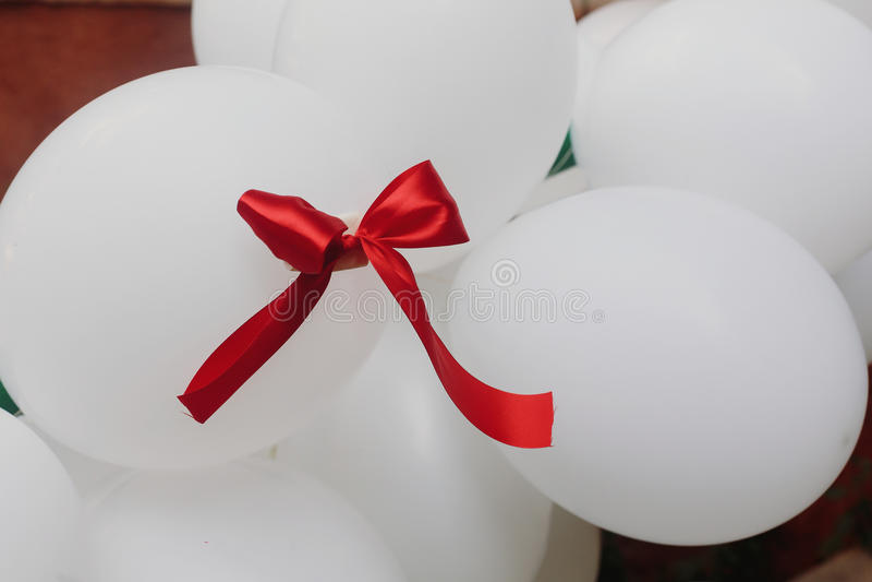 Ruban rouge sur le groupe de baloons décoratifs blancs d'air, ballons nous images stock