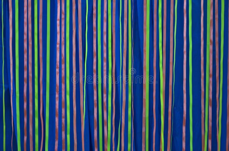 Rubans colorés accrochants sur le rideau bleu en tissu images libres de droits