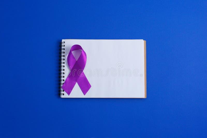 Rubans pourpres et carnet ouvert sur le fond bleu, maladie d'Alzheimer, cancer pancréatique, conscience d'épilepsie, violence f photo stock
