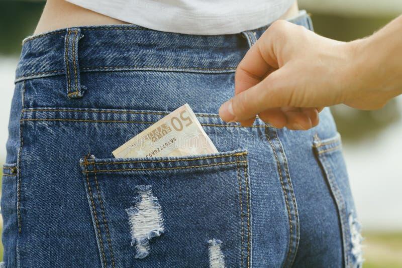 Rubare soldi dalla tasca posteriore dei jeans fotografia stock