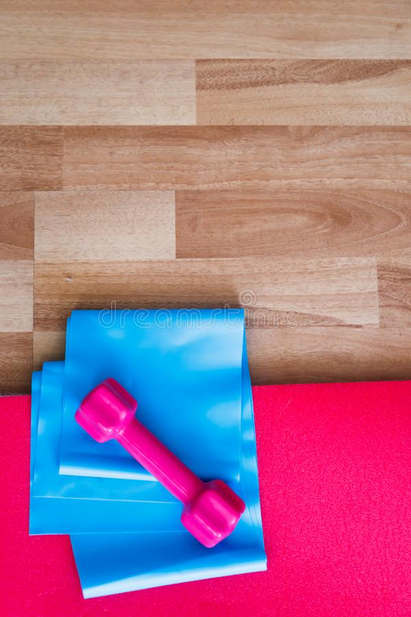 Rubber Band and Pink Dumbbell with Red Pilates Mat on Wood stock photo