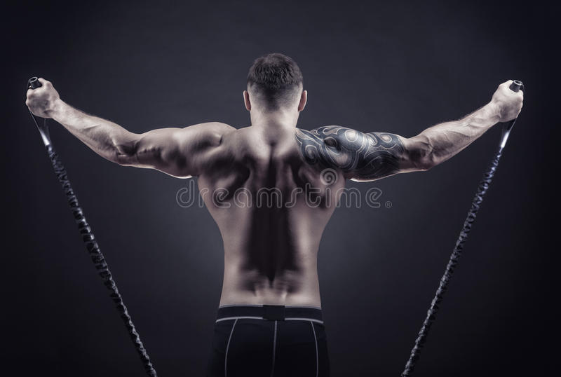 Rubber band. Sports concept. Athletic young man exercising with rubber band against a dark background royalty free stock image