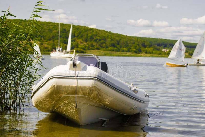 Rubber boat with engine on the sandy shore of the reservoir royalty free stock image