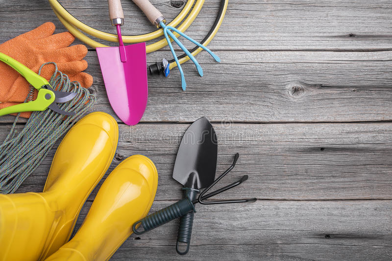 Rubber boots and garden tools. Still life on wooden boards stock photos