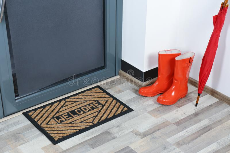 Rubber boots, umbrella and mat near door royalty free stock photo