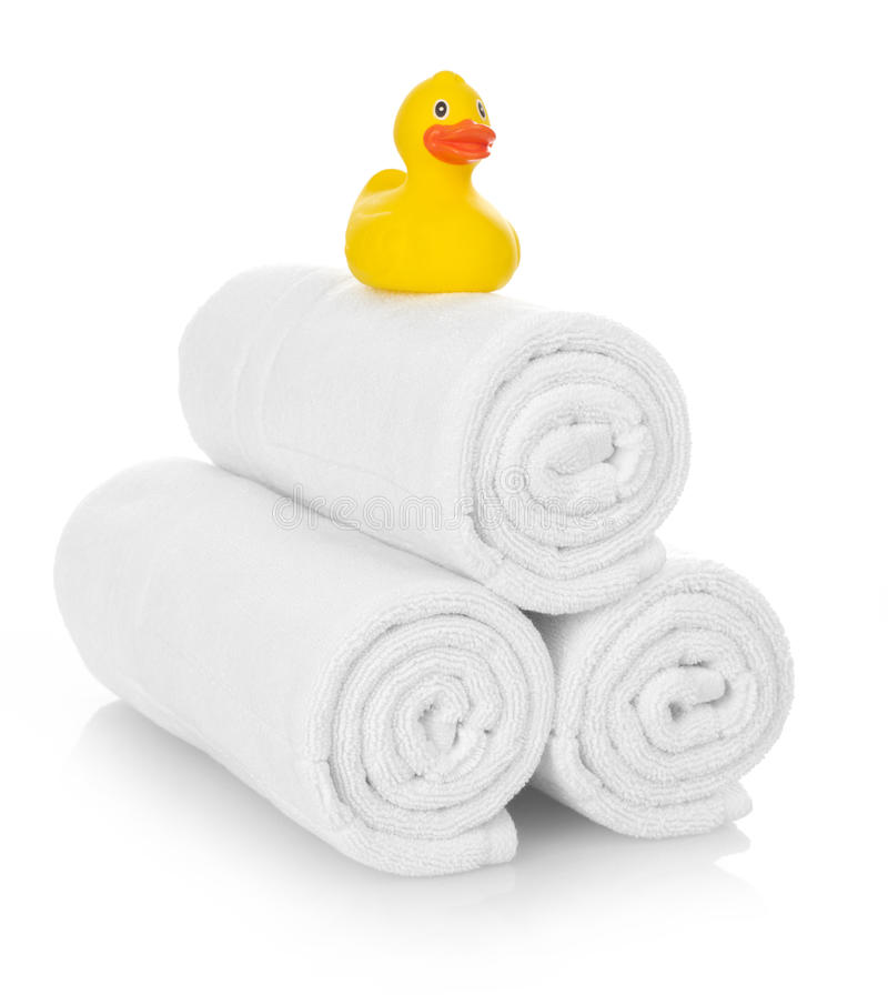 Rubber duck on white towels. On white royalty free stock images