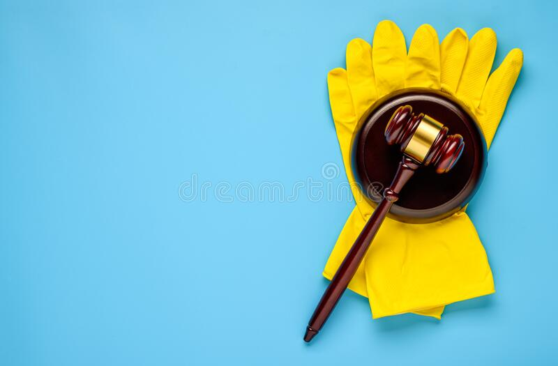 .Rubber gloves and mallet on a blue background. Concept of litigation at a cleaning company. Rubber gloves and mallet on a blue background. Concept of litigation royalty free stock photo