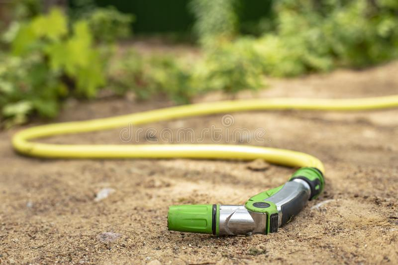 A rubber hose with a device for spraying and watering vegetation with water lies on the sandy path, against the background of a stock image