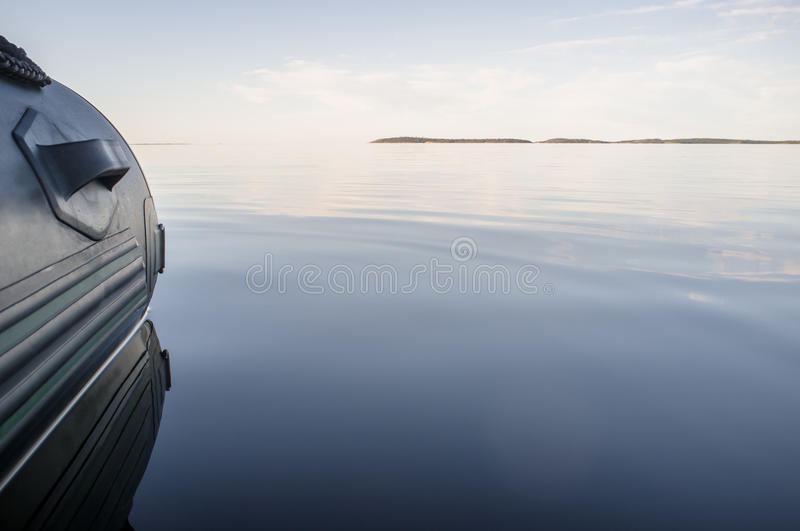 Rubber inflatable boat in calm sea. The view from the height of the water surface royalty free stock photography