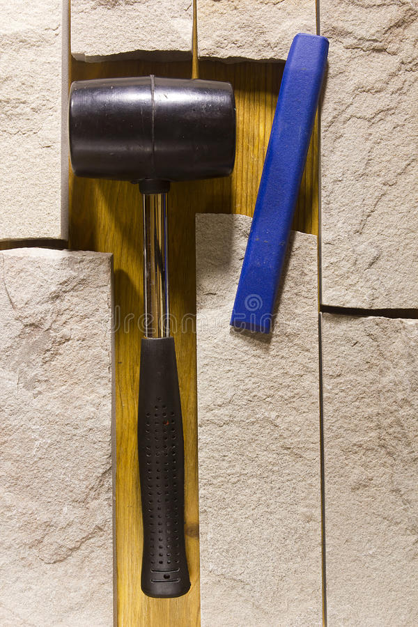 Rubber mallet and chisel. Rubber hammer and chisel on a background of stone cladding stock photography