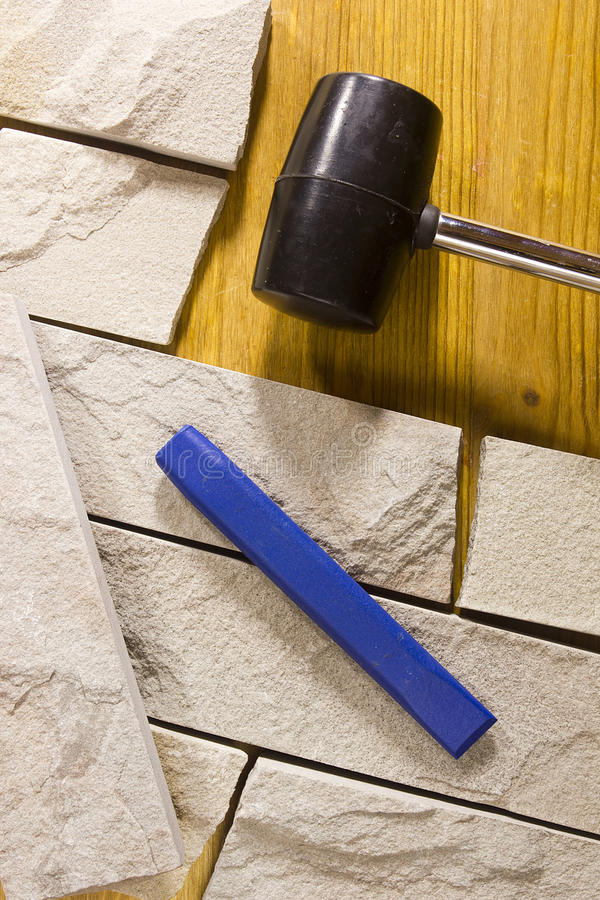 Rubber mallet and chisel. Rubber hammer and chisel on a background of stone cladding stock images