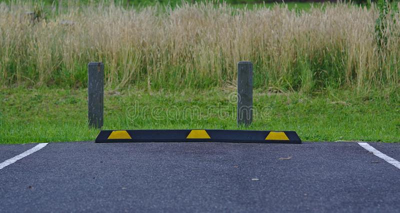 Rubber parking block in black and yellow colors. On asphalt surface with wild grass background stock photos