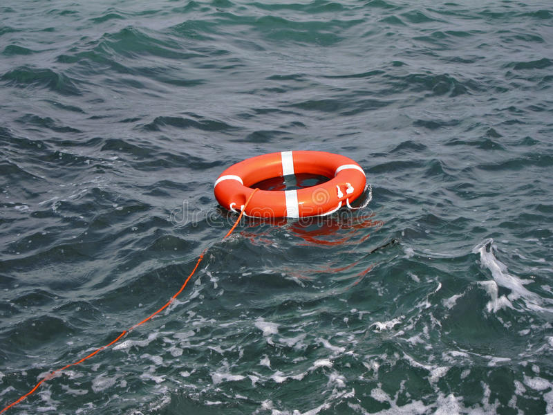 Rubber ring. Red rubber ring floating in the sea stock image