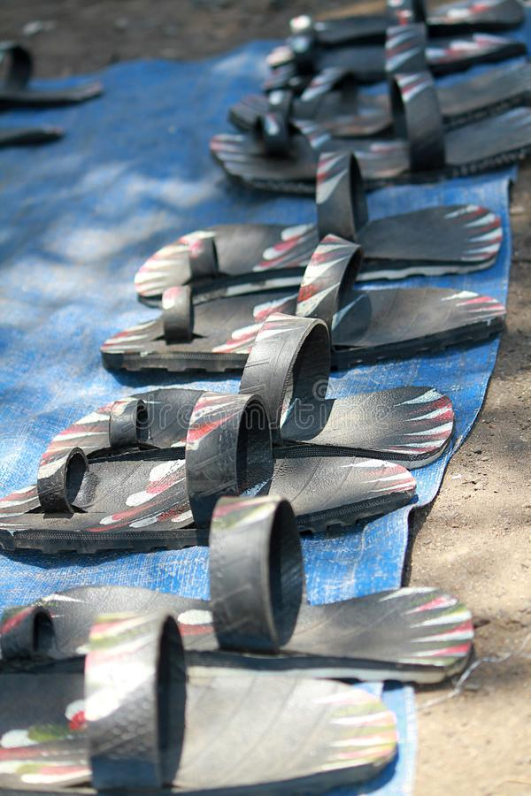 Rubber sandals made from car tires at a market in Accra, Ghana. Lined up along a street for sale to tourists stock photo